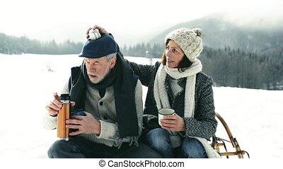 Senior couple sitting on sledge drinking tea, winter day.