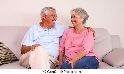 Senior couple sitting on sofa chatt