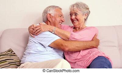 Senior couple sitting on sofa huggi