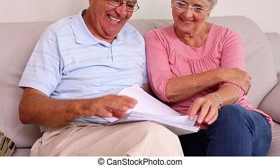 Senior couple sitting on sofa readi