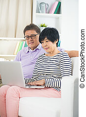 Senior Couple Sitting On Sofa Using Digital Tablet