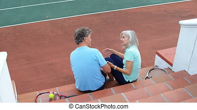 Senior couple sitting on tennis court stairs 4k - Rear view...
