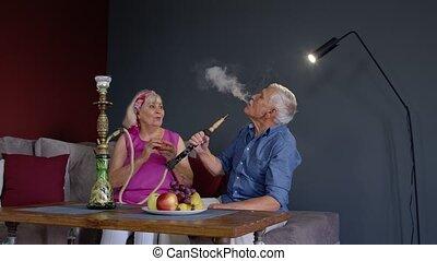 Joyful old senior couple smoking hookah, eating fruits celebrating retirement anniversary in living room at home. Elderly grandmother and grandfather having fun, enjoying relationship. 6k downscale