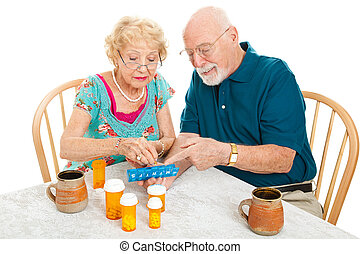 Senior Couple Sorts Medications - Senior couple at the...