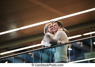 Senior couple standing at the train station, waiting, kissing