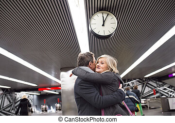 Senior couple standing at the underground platform, hugging