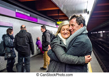 Senior couple standing at the underground platform, hugging, wai