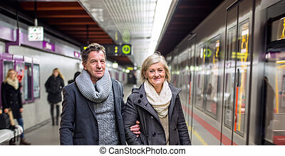 Senior couple standing at the underground platform, waiting