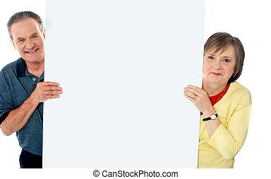 Senior couple standing behind blank billboard