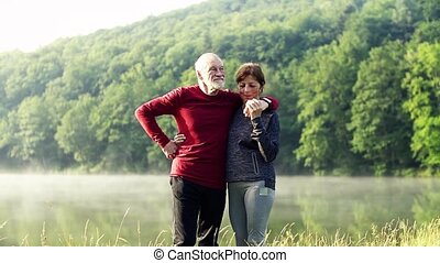 Senior couple standing by the lake outdoor in foggy morning...