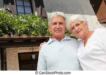 Senior couple standing in front of a house