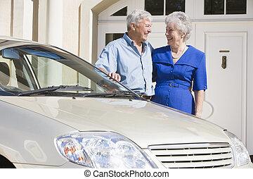 Senior couple standing next to car