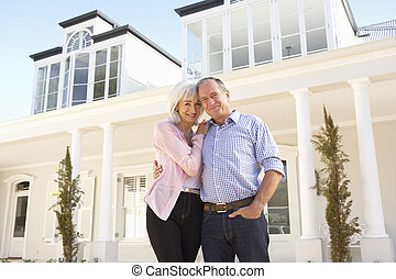 Senior Couple Standing Outside Dream Home
