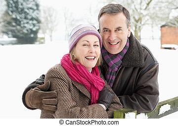 Senior Couple Standing Outside In Snowy Landscape