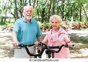 Senior Couple Stays Active - Senior couple riding bicycles...