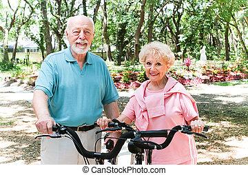 Senior Couple Stays Active - Senior couple riding bicycles...