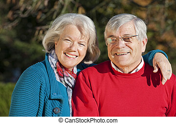 Senior couple holding thumbs up