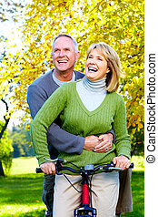 Senior couple. - Happy senior couple with bicycle in the...