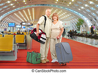 Senior couple with bags at airport