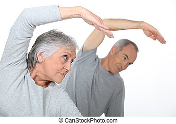 Senior couple stretching in the gym