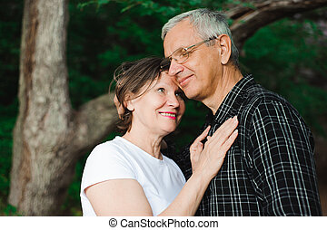 Senior couple strolling in the park. Elderly and energetic couple walk in the open air.