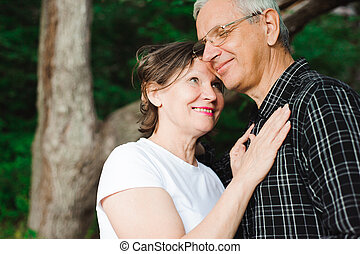 Senior couple strolling in the summer park