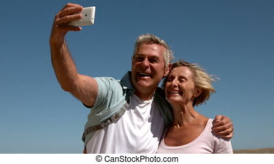 Senior couple taking a selfie - Senior couple hugging on...