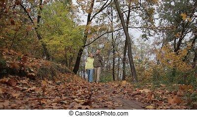 Senior couple taking a walk in park during autumn.