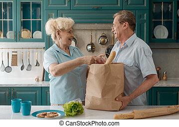Senior couple taking groceries out of a shopping bag
