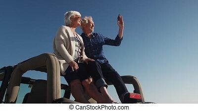 Senior couple taking photos sitting on a car