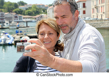 Senior couple taking picture of themselves in touristic city