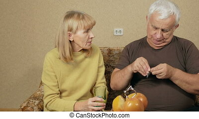 Senior couple taking pills at home. Male overweight takes a...