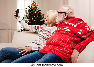 senior couple taking selfie at christmas