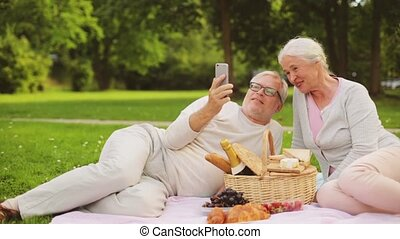 senior couple taking selfie at picnic in park - old age,...