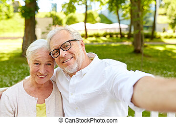 senior couple taking selfie at summer park