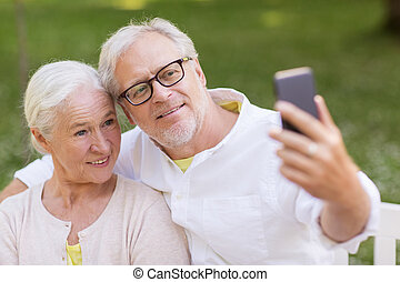 senior couple taking selfie by smartphone at park