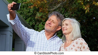 Senior couple taking selfie in homeyard 4k