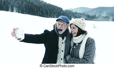 Senior couple taking selfie in winter nature.