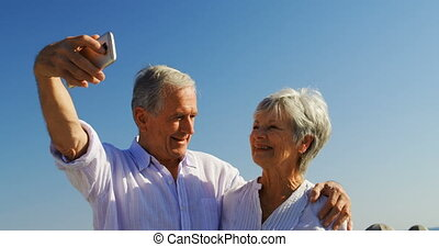 Senior couple taking selfies at promenade 4k - Smiling...