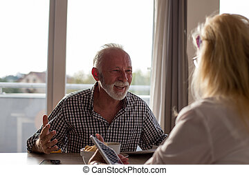 Senior couple talking at table
