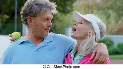 Senior couple talking in tennis court 4k - Happy senior...