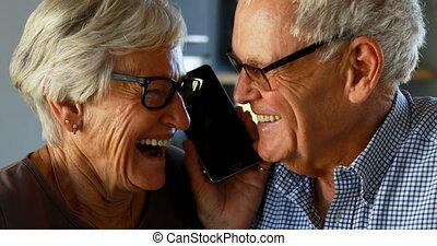 Senior couple talking on mobile phone in kitchen 4k
