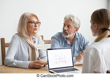 Senior couple talking to agent about house purchase at meeting
