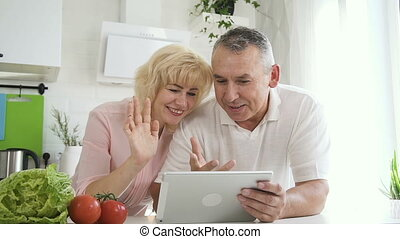 Senior couple talking to family using tablet computer.