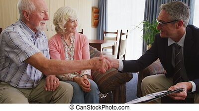 Senior couple talking with a business man in retirement house