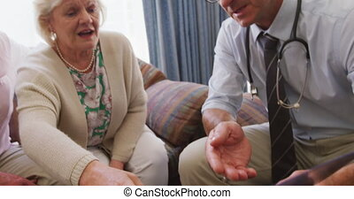 Senior couple talking with a doctor in retirement house