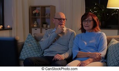 senior couple turning tv off at home in evening - leisure, ...