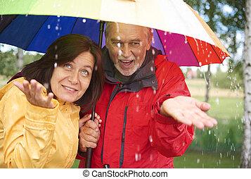 Senior couple under rainbow umbrella catching raindrop