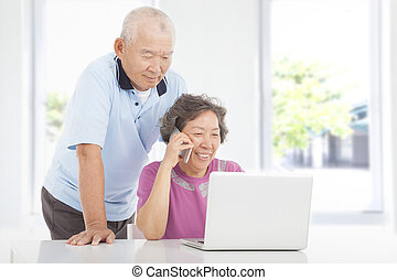 Senior couple using a laptop and a cell phone  at home