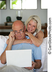 Senior couple using at laptop